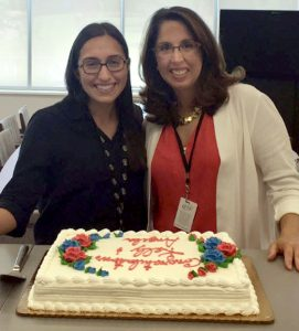 """Angela and Kelly """"take the cake"""" at a surprise party given by their ETS co-workers in honor of their paper being named the best contributed paper at SLA 2016."""